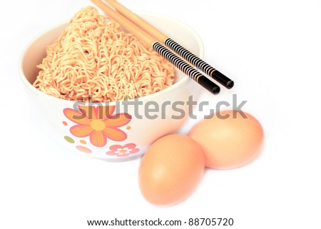 Dry instant noodles in bowl with eggs and chopsticks. Isolate on white background. Focus at noodles. - stock photo