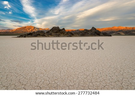 Dry lake bed on sunset, with cracked mud on a lake floor blue sky, clouds and mountains. Racetrack Playa. Death Valley national park. California. USA.  - stock photo