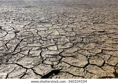 Dry lake bed with natural texture of cracked clay in perspective floor. Death Valley field . background. Selective focus on black soil dark land. Idea concept symbol disaster ecology in nature - stock photo