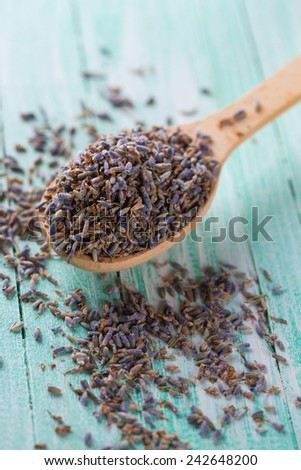 Dry lavender buds in spoon on green painted wooden planks. Selective focus. - stock photo
