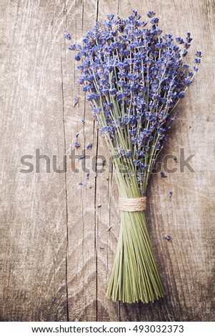 Dry lavender bunch on vintage wooden table top view. Rustic style.
