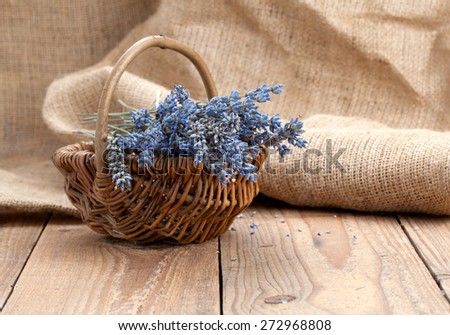 dry lavender flower in a basket, on wooden background - stock photo