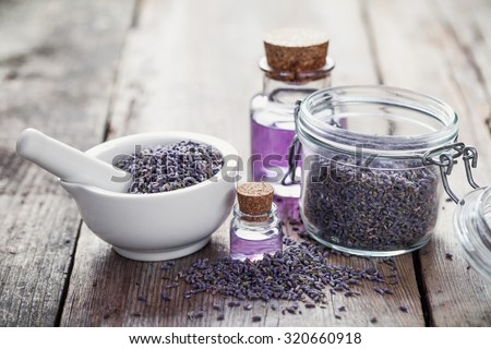Dry lavender flowers in white mortar, glass jar of lavender and bottles of essential oil.  Selective focus - stock photo