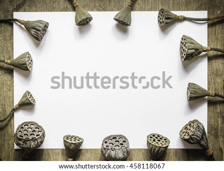Dry lotus with white paper on wooden table background