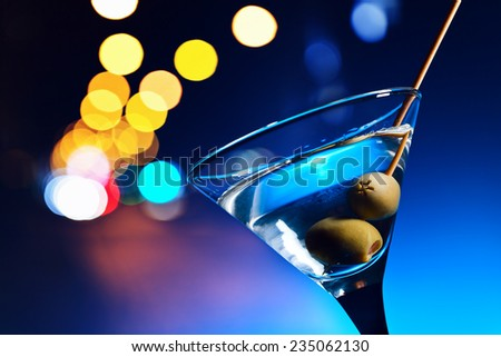 dry martini with olives ,focus on a berry - stock photo