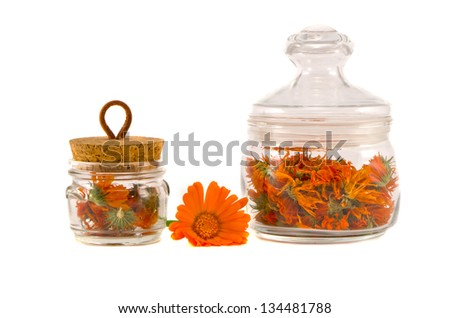 dry medical herbs calendula in glass jars isolated on white - stock photo