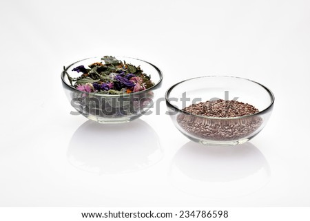 Dry medicinal herbs and seeds in glass bowls (flax seeds, clitoria, rose, calendula, daisy, sage) - stock photo