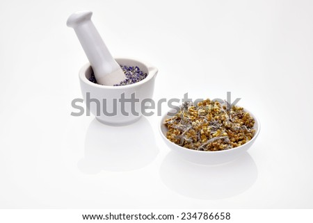 Dry medicinal herbs immortelle and cornflower in porcelain bowl and mortar with pestle - stock photo
