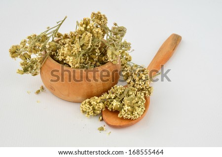 Dry Milfoil flowers - Achillea Millefolium in a small wooden bowl with wooden teaspoon isolated in white background - stock photo