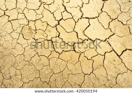 Dry mud with many cracks and fissures on the surface - stock photo