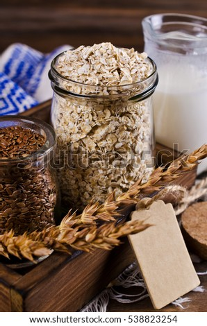 Dry oat flakes with flax seeds and milk on a dark wooden background. Selective focus.