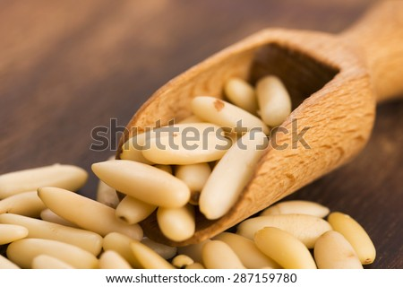 Dry Organic Pine Nuts on Wooden Background
