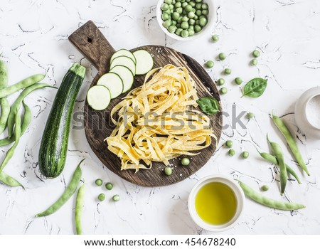 Dry pasta tagliatelle, zucchini, green beans and peas, olive oil on a light background. Vegetarian food - stock photo