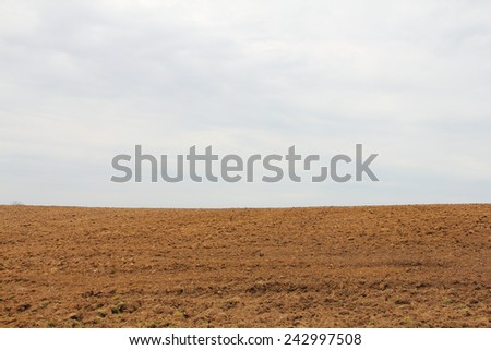 Dry plowed earth agricultural land hill and sky background - stock photo