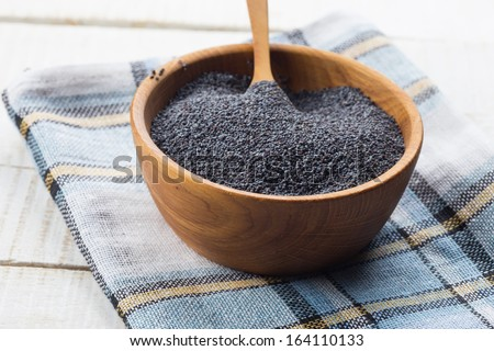 Dry poppy seeds in wooden bowl on white table. Rustic style. Selective focus.