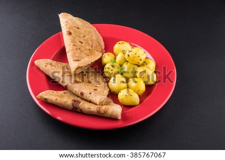 dry potato curry or potato bhaji or aalu bhaji and chapati or paratha or kulcha or indian bread, indian meals, indian breakfast or lunch or dinner item