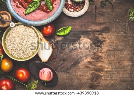 Dry quinoa with tomatoes and cooking ingredients on dark wooden background, top view, border, place for menu or recipe