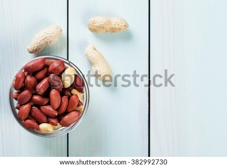 Dry roasted peanuts and peanut pods on blue table - stock photo