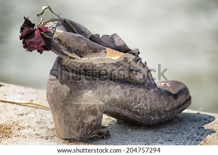 Dry rose on bronze  shoes on the Danube bank, holocaust memorial on the Pest side of the Danube river promenade honouring the jews killed during the world wide war II - stock photo