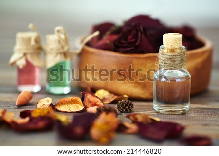 Dry rose petals and aromatic essences in small bottles - stock photo