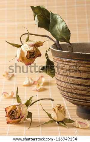 Dry rose with wilted green leaves in an old wooden bowl and dried rosebuds and petals on a straw mat