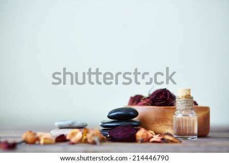 Dry roses in bowl, spa stones and aromatic essence in bottle - stock photo