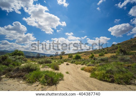 Dry sand and brush fill a riverbed during drought climate in the American southwest. - stock photo