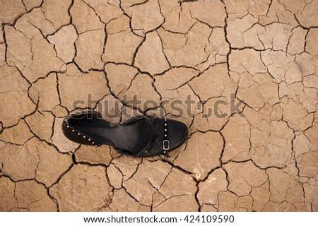 Dry soil and a black womens shoe. - stock photo