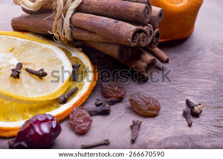 dry spices, raisins, cinnamon, cloves, rose hips on a wooden background close-up - stock photo