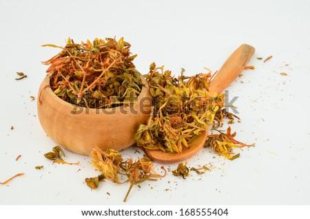 Dry St. John's Wort - Hypericum Perforatum in a wooden bowl with teaspoon - stock photo
