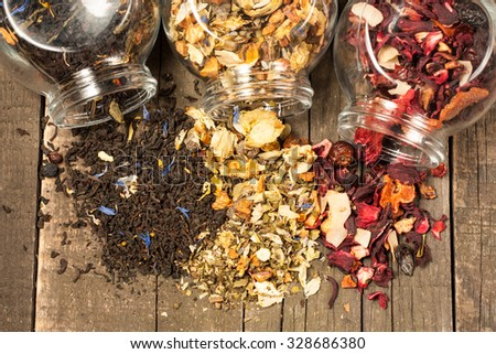 Dry tea in glass jars on wooden rustic background. Leaves of red, green and black tea. Macro photo. Rustic style and concept. - stock photo