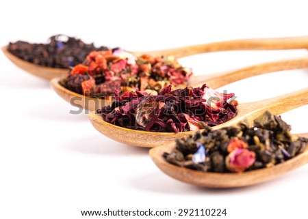 Dry tea in wooden plates and spoons, on white background. Leaves of red, green and black tea. Macro photo. Rustic style and concept. - stock photo