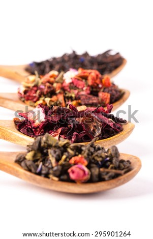 Dry tea in wooden plates and spoons, on white background. Leaves of red, green and black tea. Macro photo. Rustic style and concept.