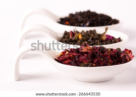 Dry tea inwhite bowls on white background. Leaves of red, green and black tea. Macro photo. - stock photo