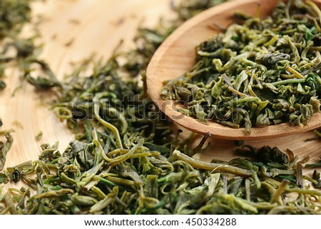 Dry tea leaves in wooden spoon, close up