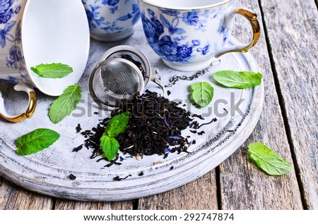 Dry tea with fresh mint leaves on wooden background - stock photo