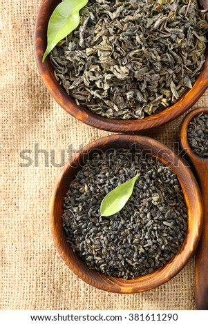Dry tea with green leaves in wooden bowls on burlap background