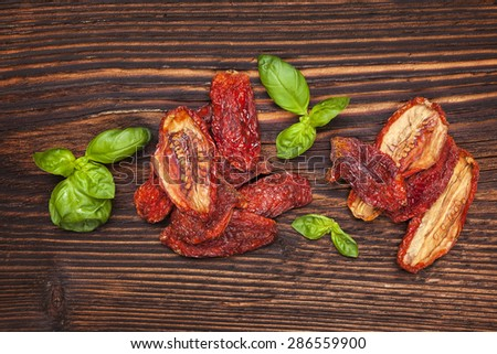 Dry tomatoes and fresh basil leaves on brown wooden background, top view. Italian eating, rustic styles. - stock photo