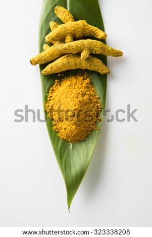 dry Turmeric and turmeric powder over green leaf on white background,  vertical top view - stock photo