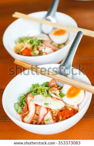 Dry yellow noodles with egg and pork in white bowl with spoon and wood chopsticks on wood table. Thai food.