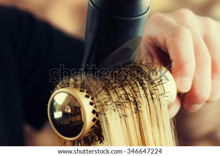 Drying blond hair with hair dryer and round brush.