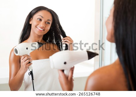 Drying hair in bathroom. Rear view of beautiful young African woman drying hair and smiling while standing in bathroom and against a mirror  - stock photo