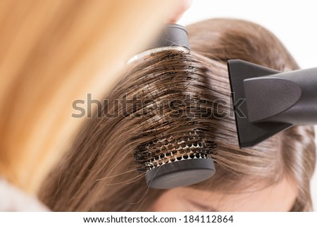 Drying long brown hair with hair dryer and round brush. - stock photo
