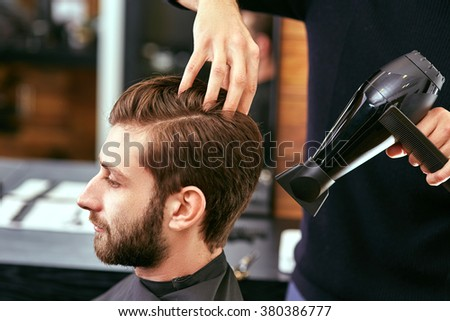 drying, styling men's hair in a beauty salon
