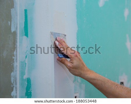 drywall hydrophobic plasterboard in green plastering seam with trowel - stock photo