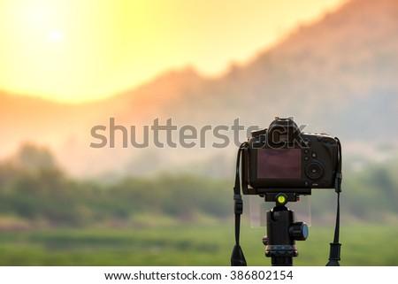 DSLR camera focus on sunrise landscape view. - stock photo