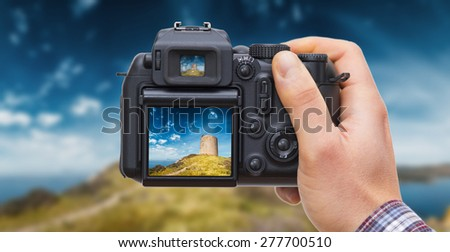 DSLR camera in hand shooting landscape with ancient watchtower -these are photos made by me, that you separately find on my shutterstock portfolio. Logos, brand,has been deleted to be 100% commercial. - stock photo