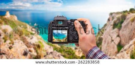 DSLR camera in hand shooting seascape - these are all photos made by me, that you separately can find on my shutterstock portfolio. Logos, brand, or anything has been deleted to be 100% commercial. - stock photo