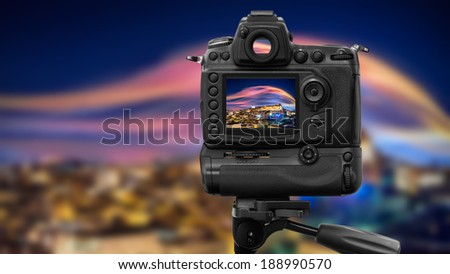 DSLR Camera on tripod shooting night city with aurora borealis - stock photo