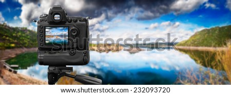 Dslr camera shooting in a calm lake - stock photo